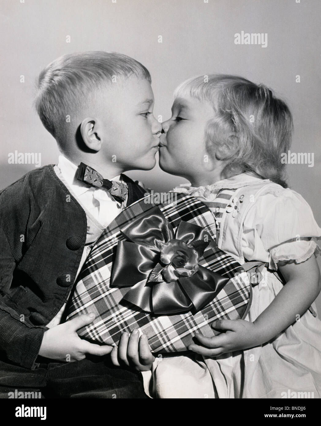 Close Up Of A Boy And A Girl Holding A Valentine Gift And Kissing