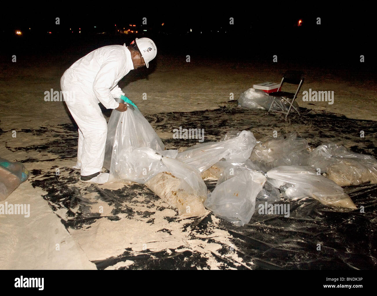 A night crew worker wearing a Tyvek suit, bags up large quantities of oil from the British Petroleum oil spill on - Stock Image