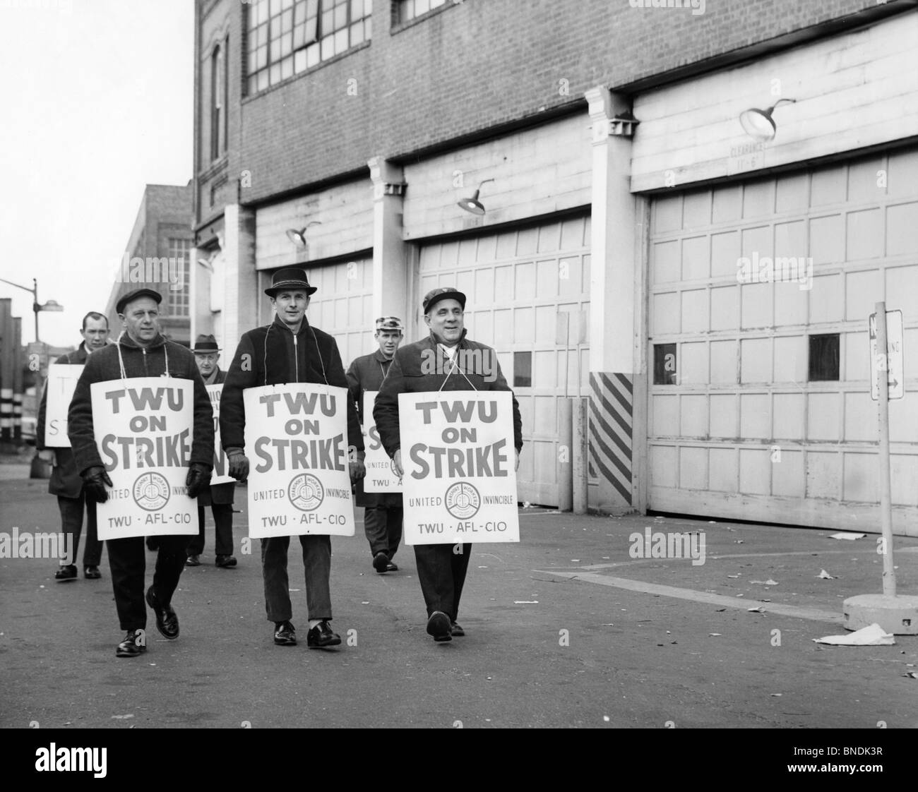 Group of people walking on a street holding placards - Stock Image