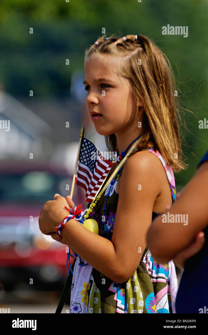 Young Girl Holding American Flag while Watching the Oldest Continuous Independence Day Parade in America in New - Stock Image
