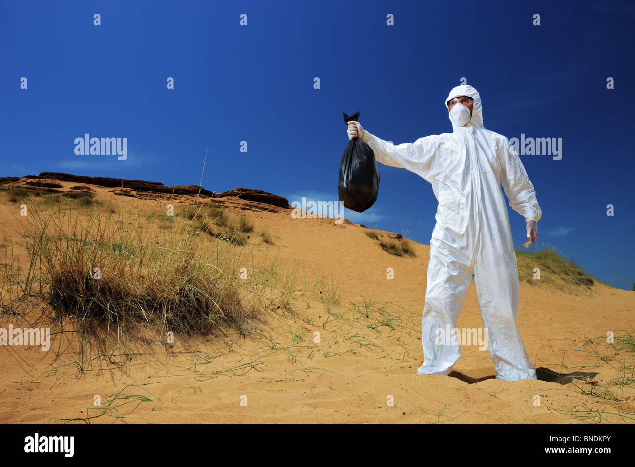A man in a protective suit holding a waste bag - Stock Image