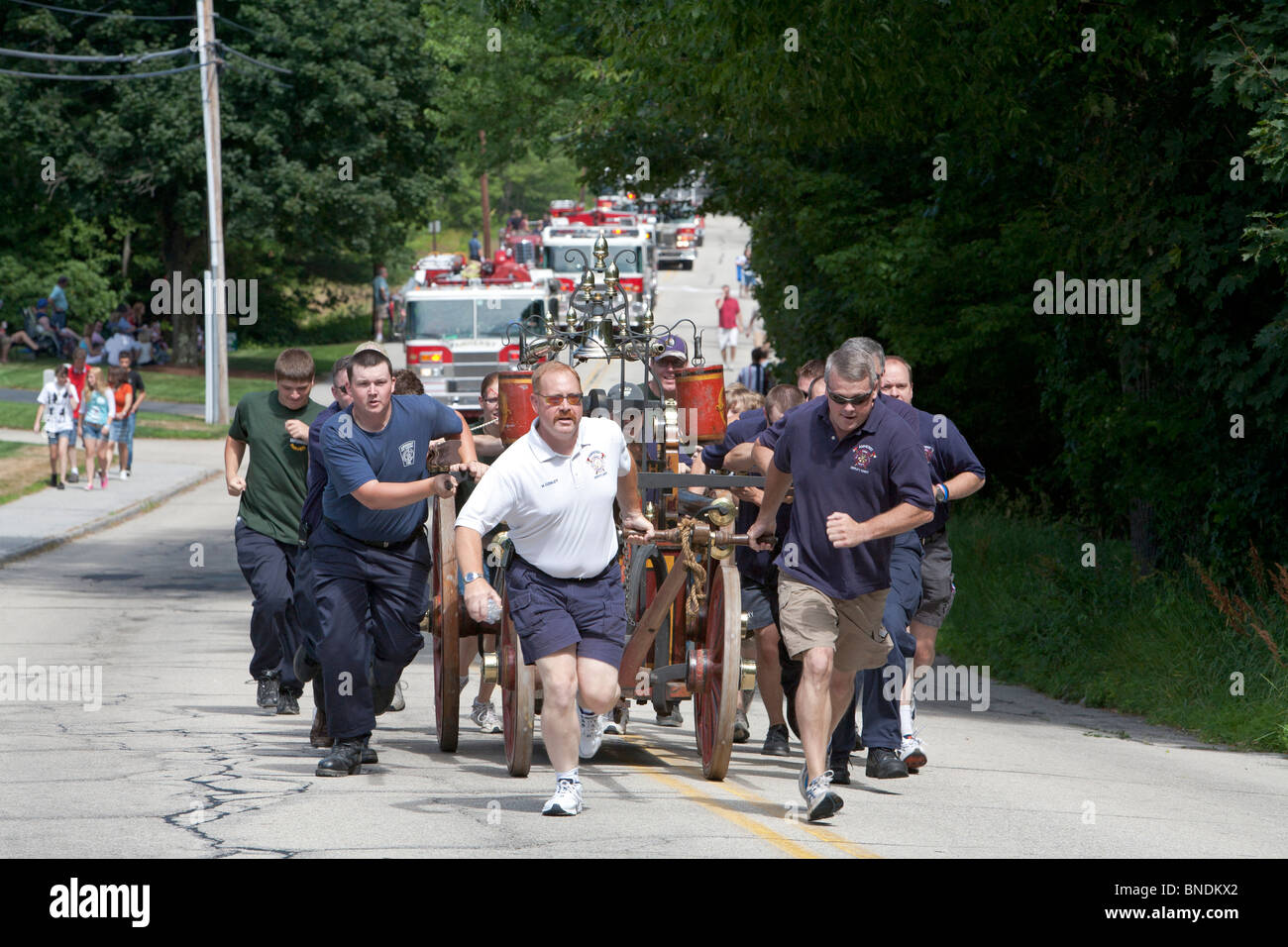 Volunteer Firefighters Pull Antique Pumper in July 4 Parade - Stock Image