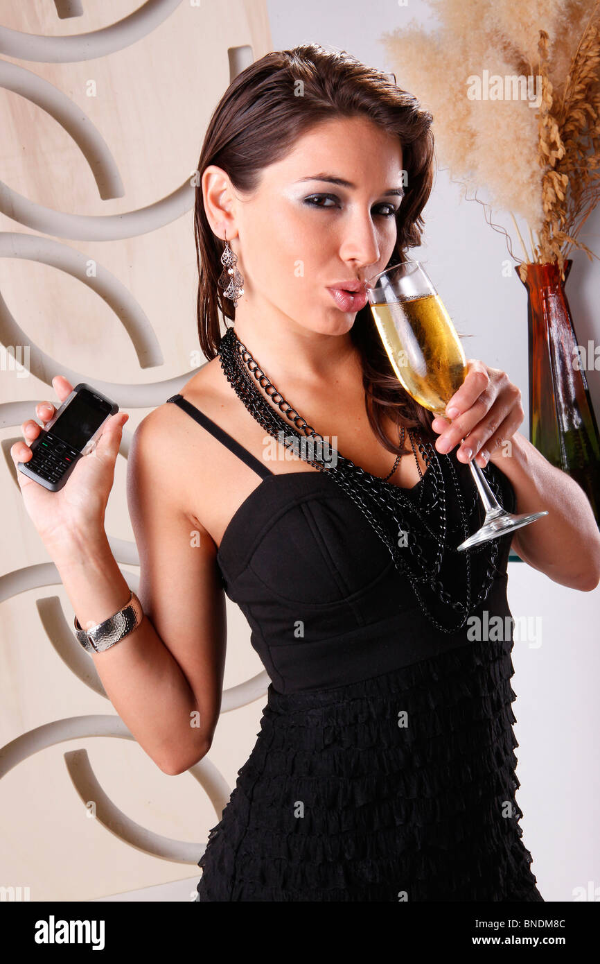 Cute brunette on a cell call while having wine - Stock Image