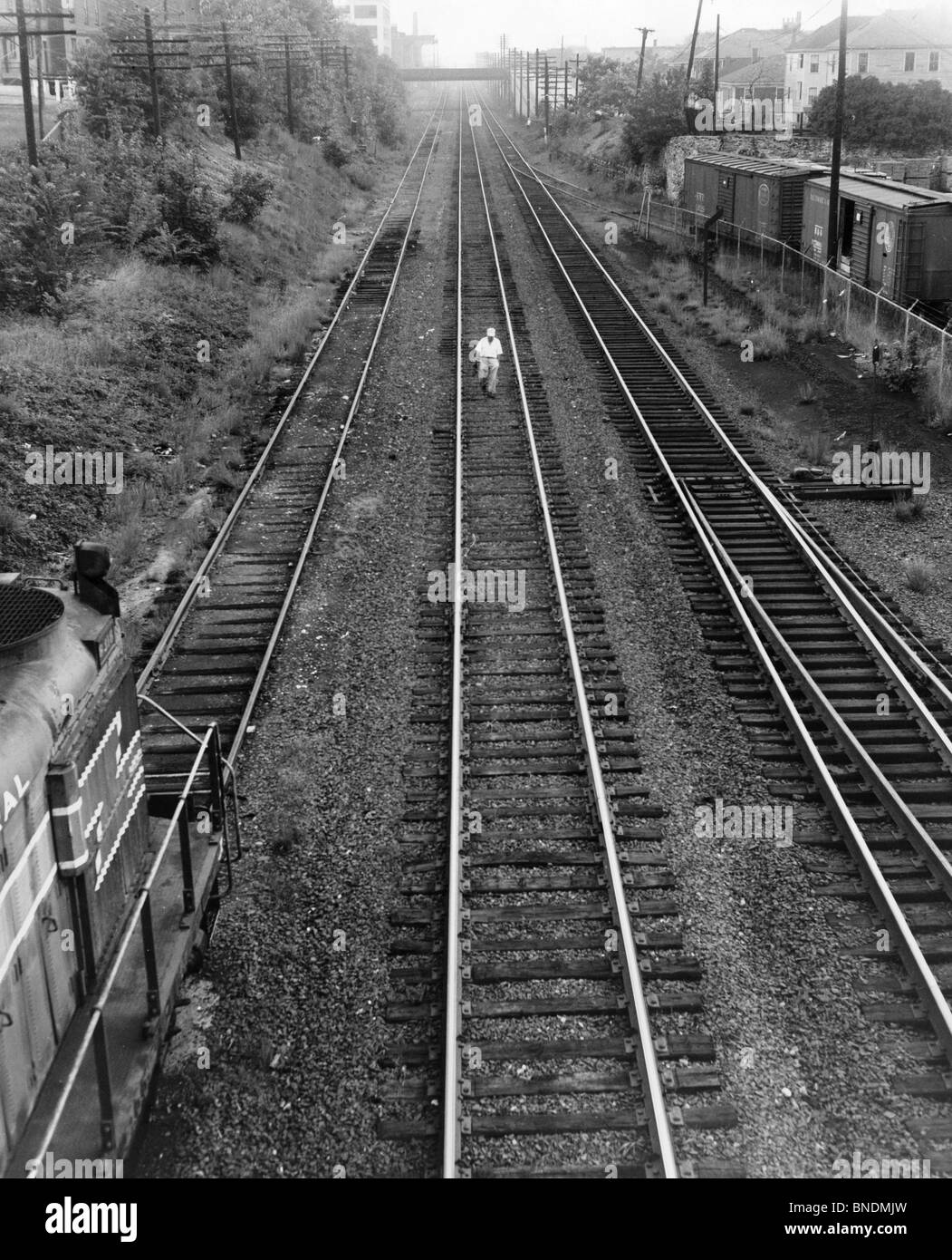 High angle view of a man walking on railroad tracks - Stock Image