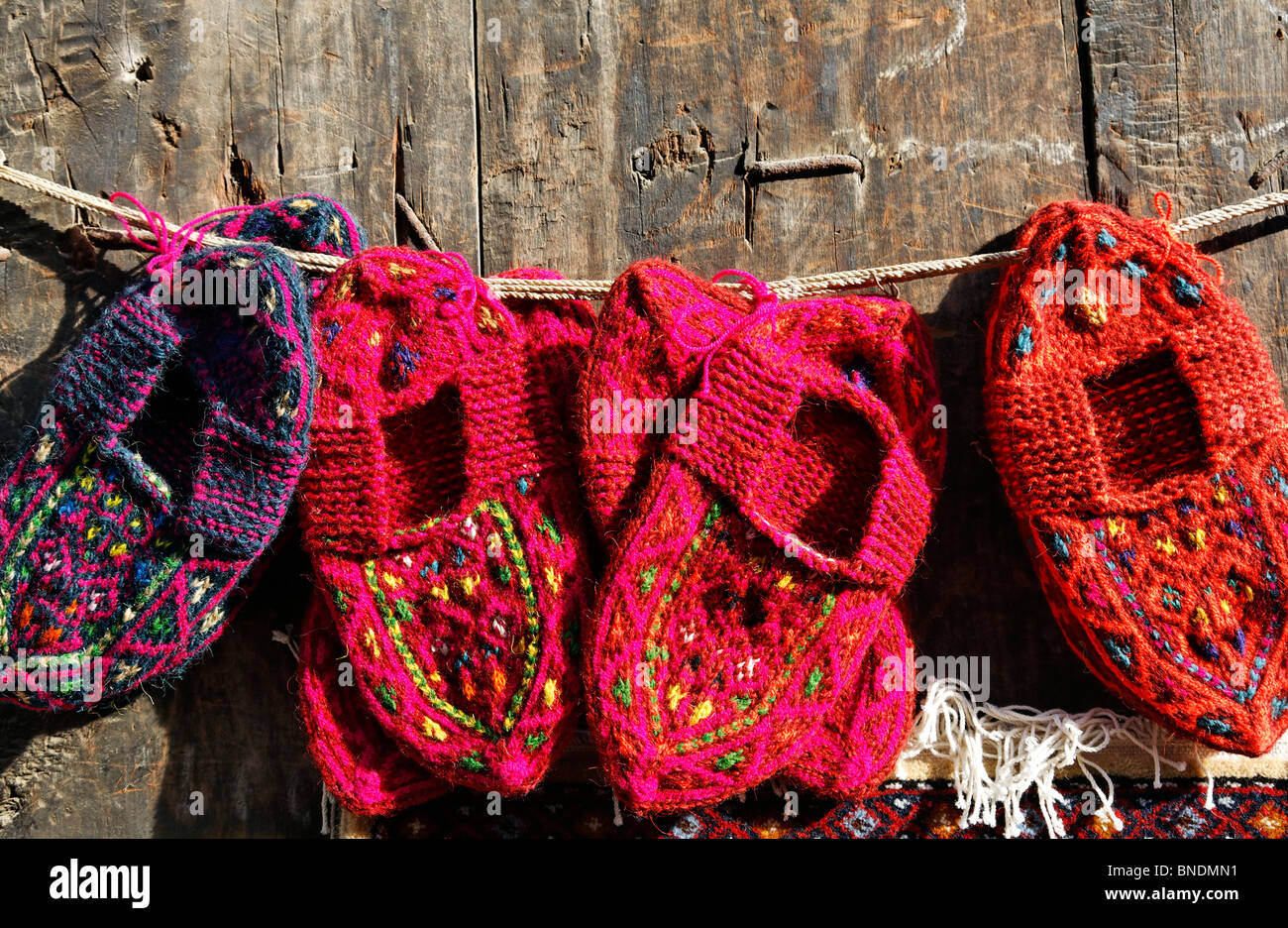 Display of woollen baby shoes outside a shop, Lahic village, Azerbaijan - Stock Image
