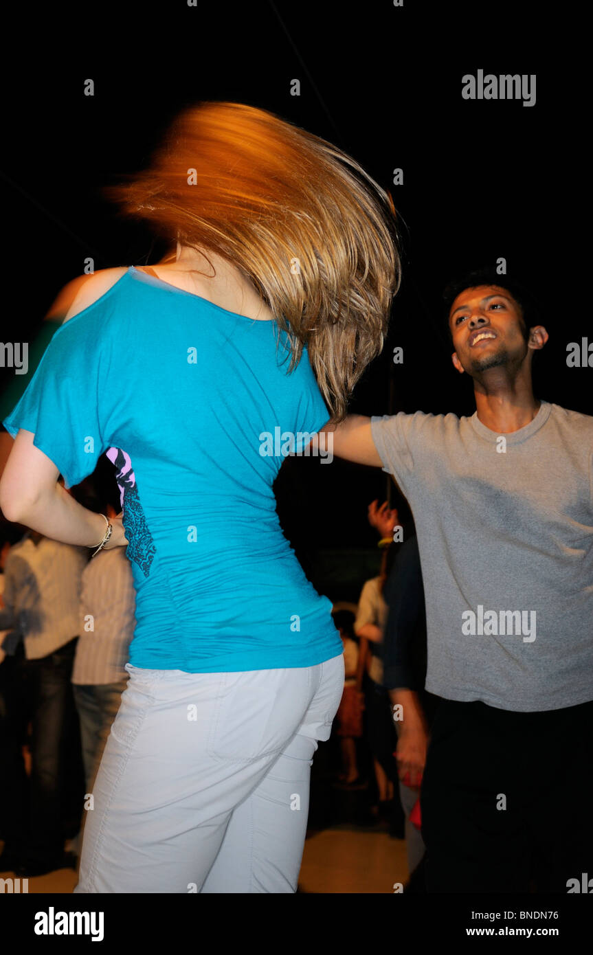 Young male swinging a female salsa dancer on a boat cruise at night Toronto - Stock Image