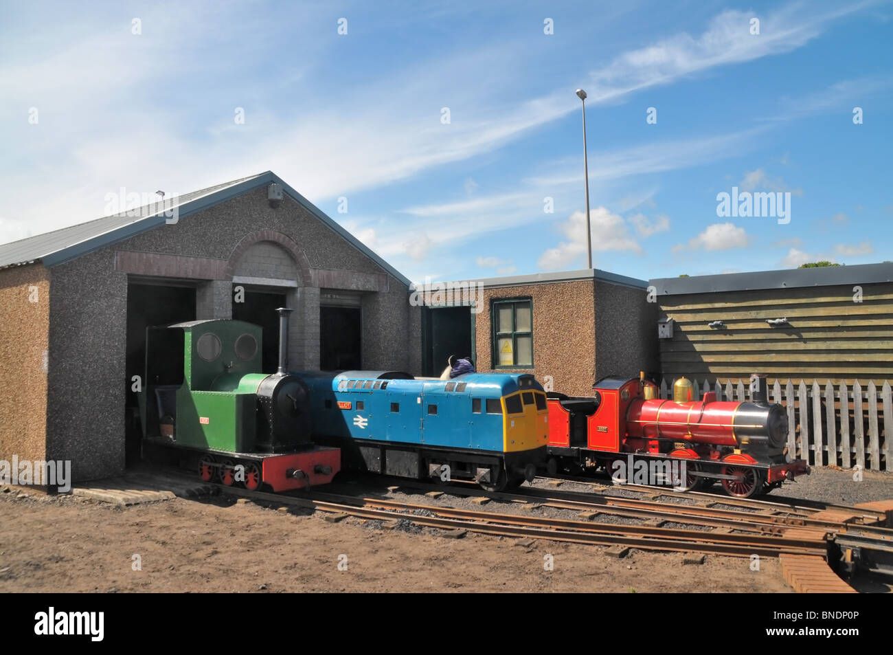 old types of train engines stationed at the sidings of a miniature but operational railway. - Stock Image