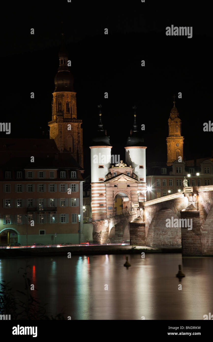 Historic old Heidelberg Bridge beautiful night lights, reflections in soft flowing Neckar River water, church towers - Stock Image