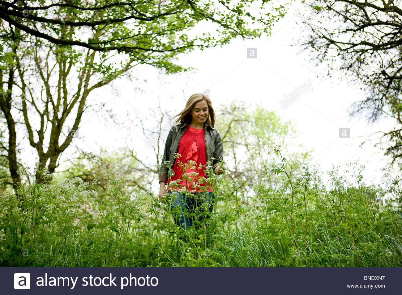 A young woman walking through long grass - Stock Image