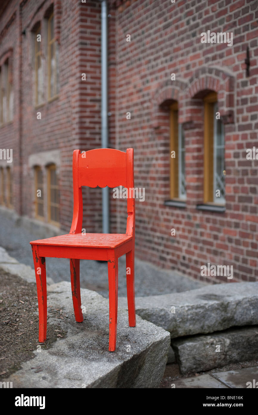 Bright orange antique wooden chair standing in front of an old brick building - Stock Image