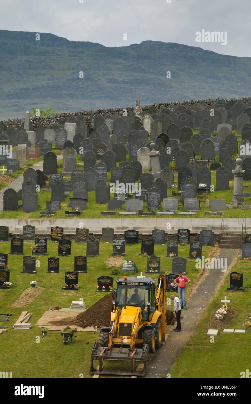 Contractor digging grave with a JCB digger in Steshon village near Trawsfynydd, Snowdonia National Park, Gwynedd - Stock Image