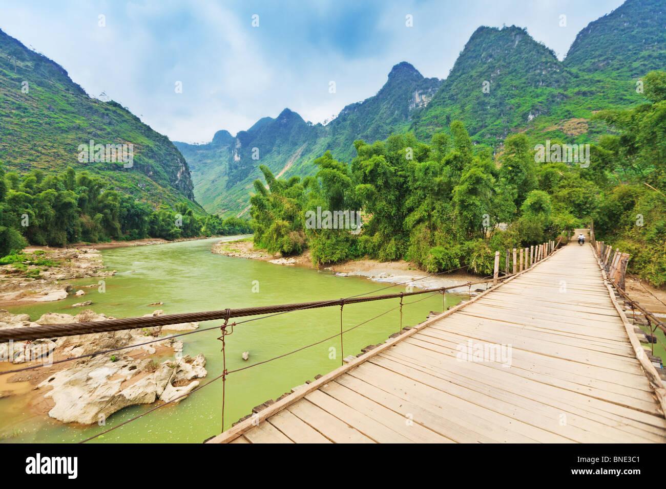 Wooden bridge over mountain river. Northern Vietnam - Stock Image