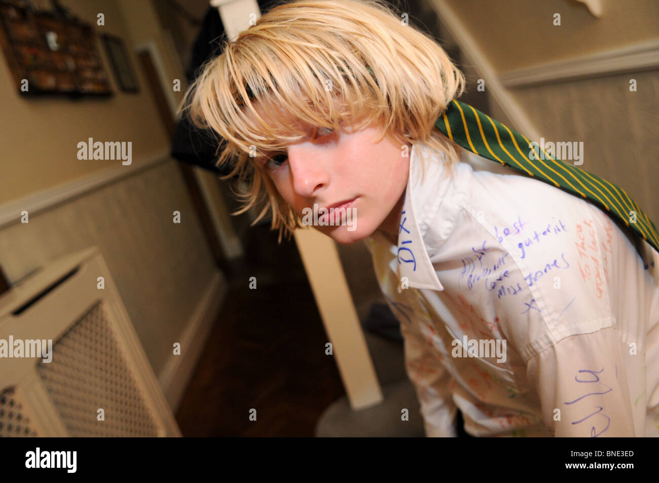 Year 6 schoolboy with tie around his head and writing on his shirt after celebrating leaving junior school sitting - Stock Image
