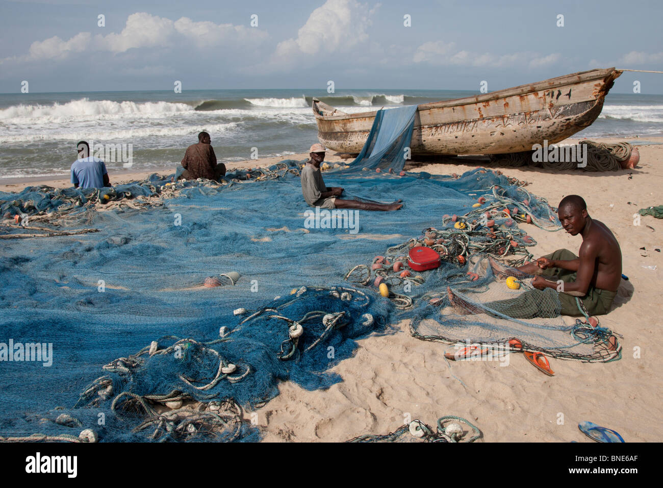 Fishermen repairing their nets beside their sea-going dugout canoe on the beach beside the village of Akosu, near - Stock Image