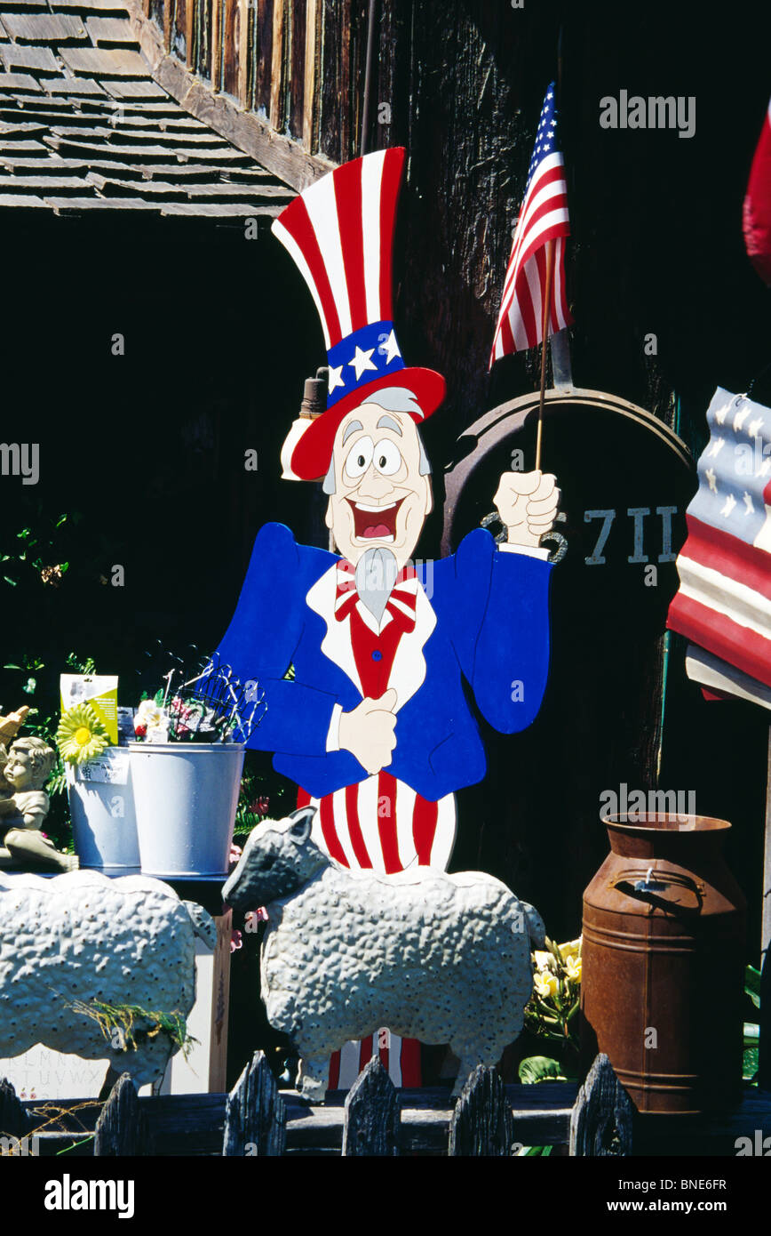 Cartoon character wearing bowler hat painted in American flag colors, holding American flag in theme park Stock Photo