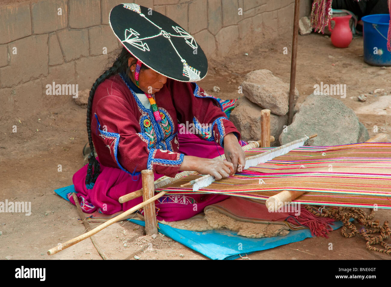 A peruvian woman in traditional dress weaving a blanket in the plaza in Racchi, Peru, South America. - Stock Image