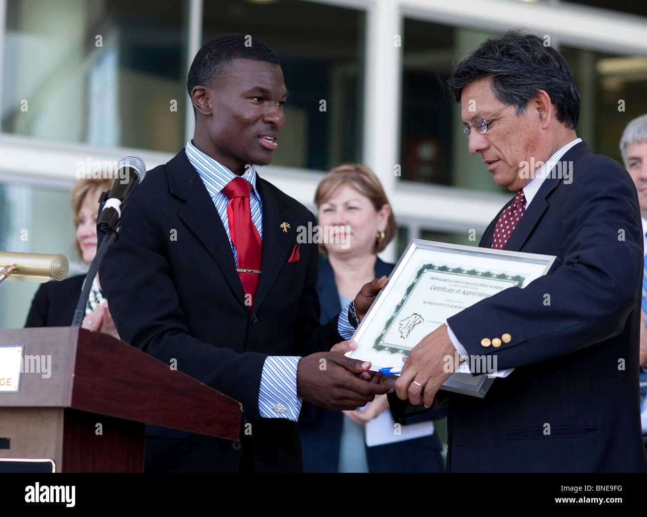 African-American student at Garza Early College High School at Brookhaven College presents an award to a state legislator - Stock Image