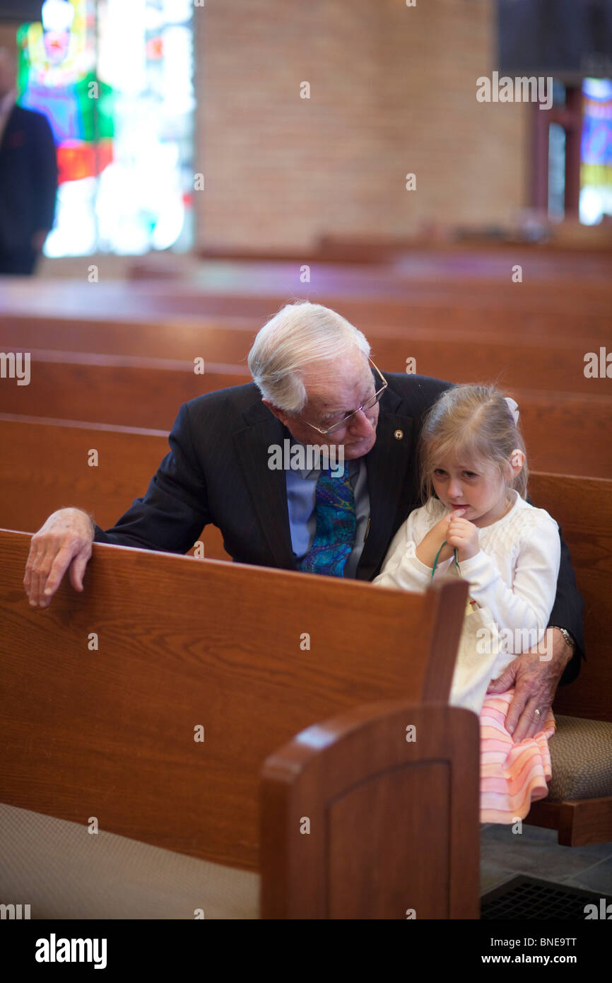 Grandfather comforts young granddaughter in church pew after service - Stock Image