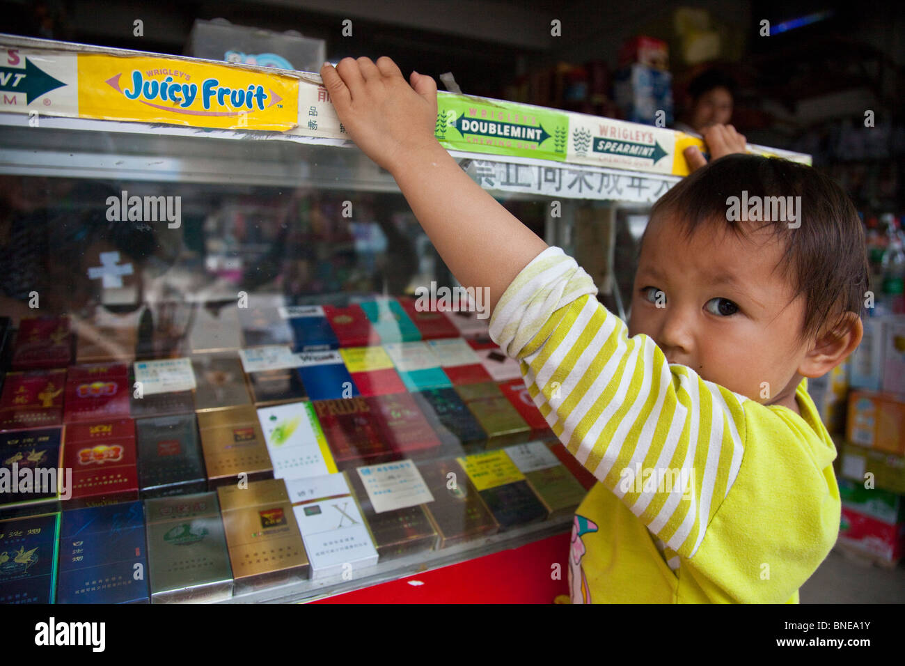 Little girl at the cigarette counter of her family convenicence store in Xingping, Guangxi Province, China Stock Photo