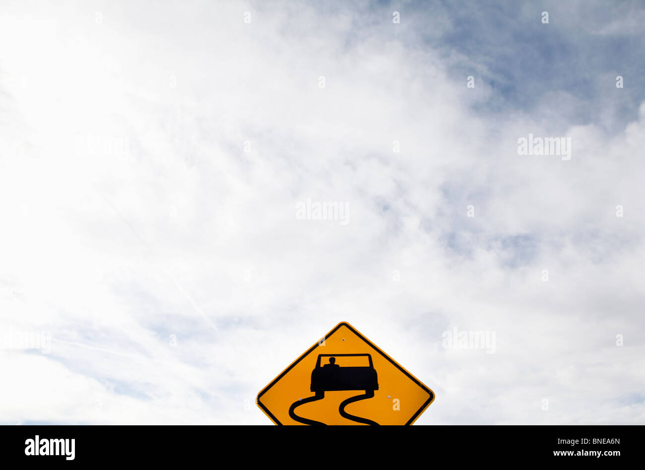 Slippery Road sign against a clouded sky Stock Photo