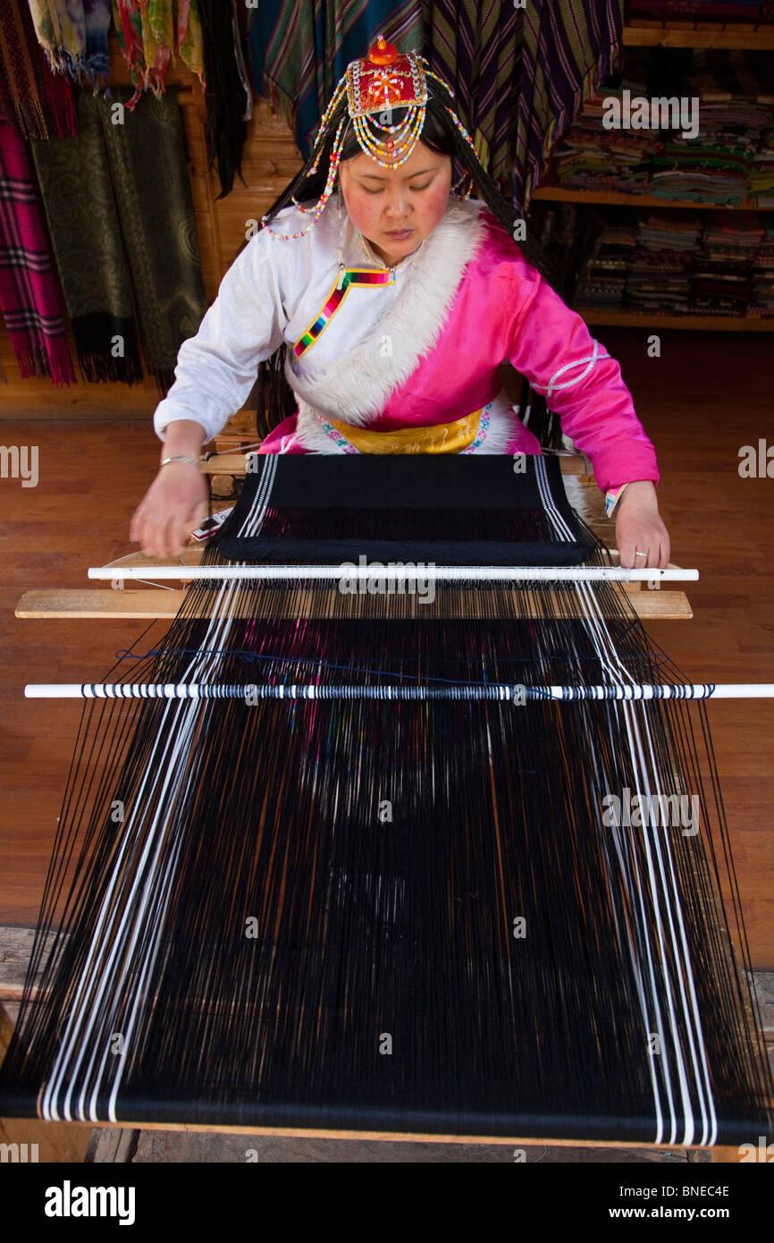 Minority woman weaving in Shangri-La or Zhongdian in Yunnan Province, China - Stock Image