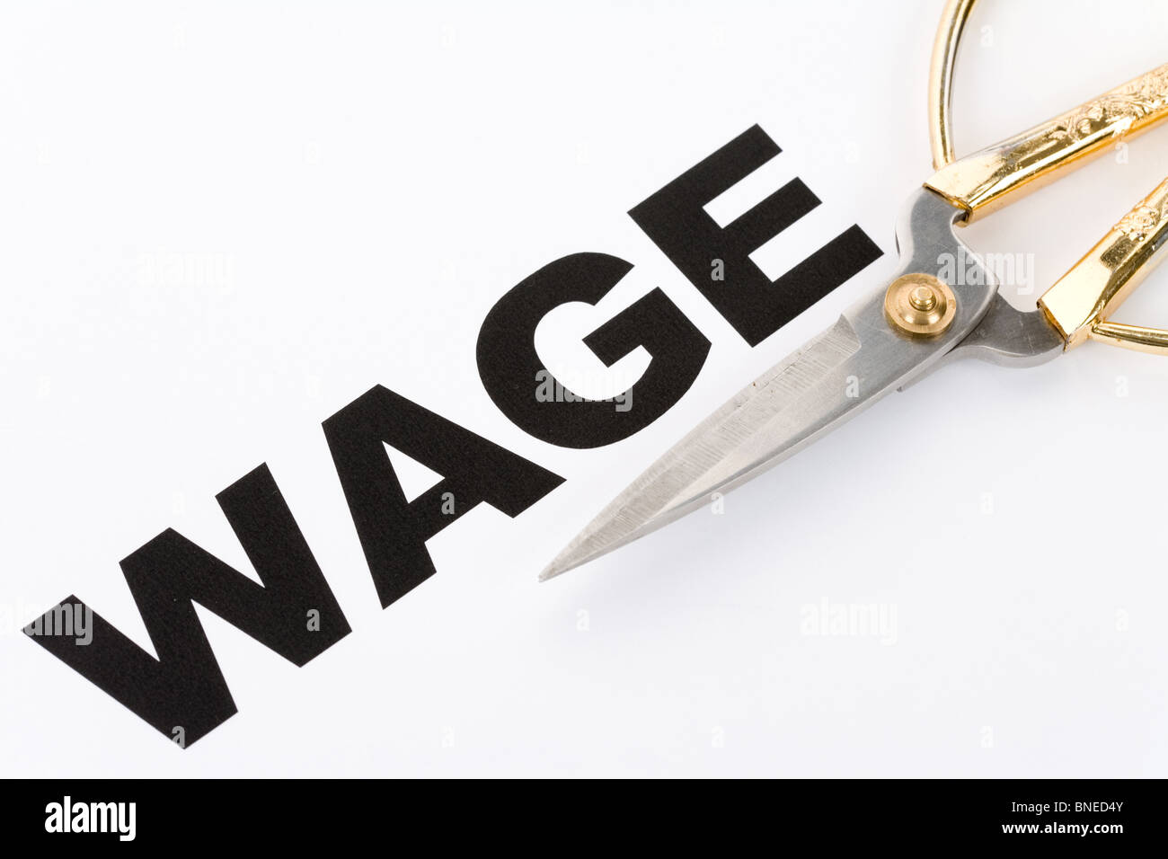 text of wage and scissors, concept of salary cut - Stock Image