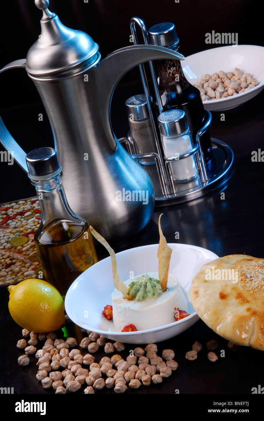 Arabic food humus,arranged with traditional kettle,olive oil and peas. - Stock Image