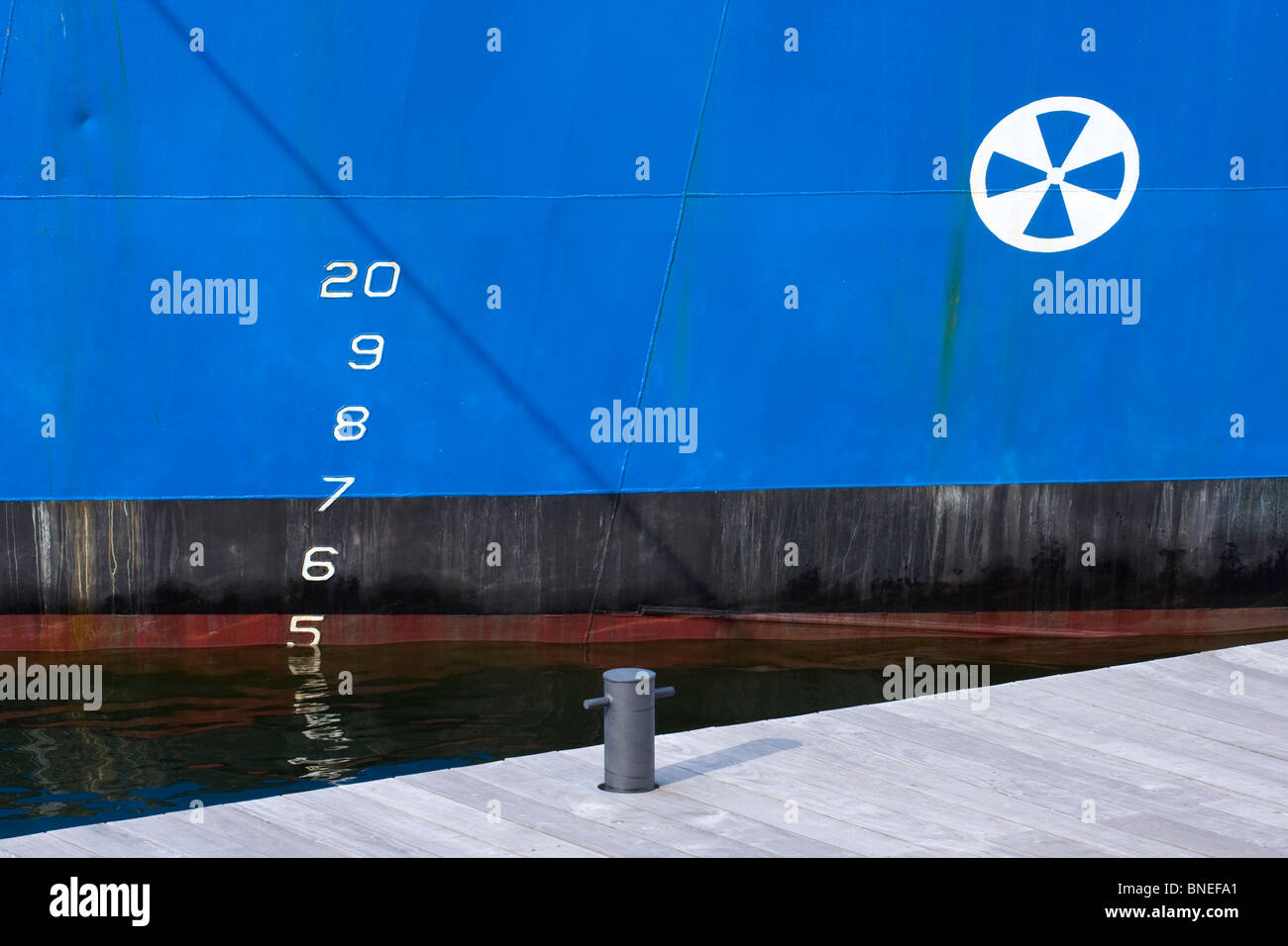 Steel Hull of Blue Boat in water with Draft Markings and Pier Cleat on Dock. - Stock Image