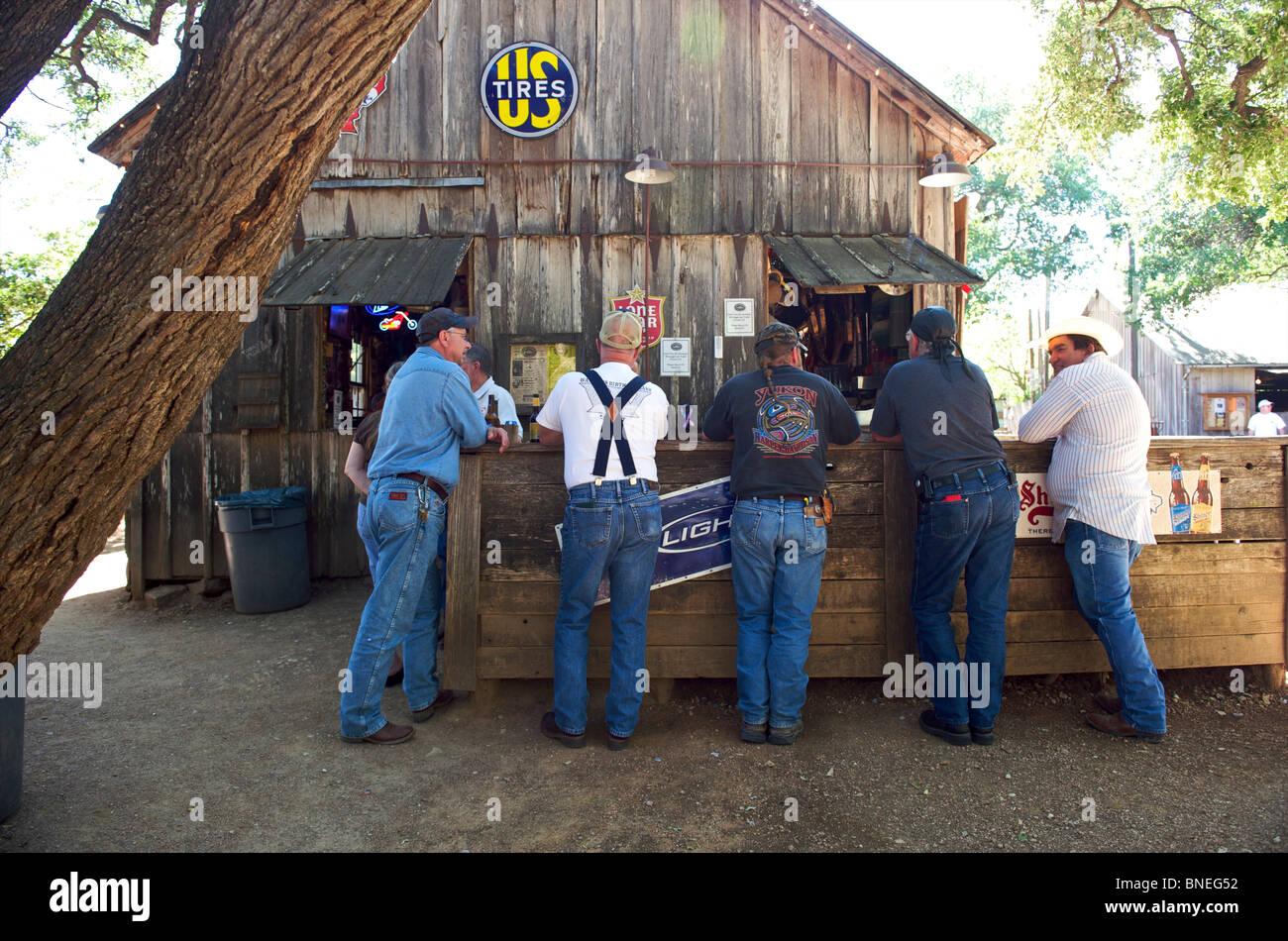 Men standing at outdoor bar in Luckenbach, Taxes, USA Stock Photo