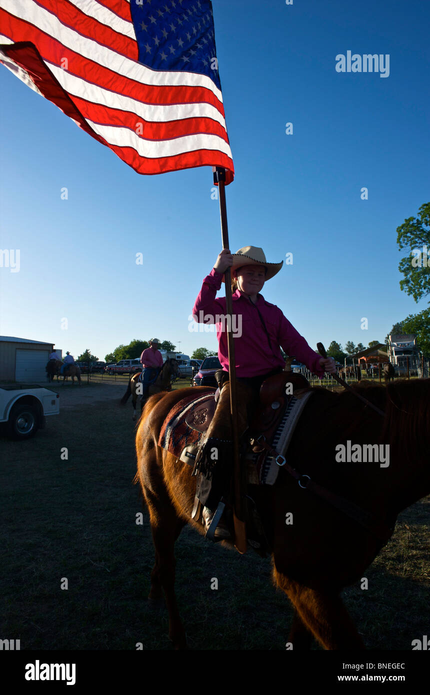 Cowgirl waving American flag at opening ceremony of PRCA rodeo event in Texas, USA Stock Photo
