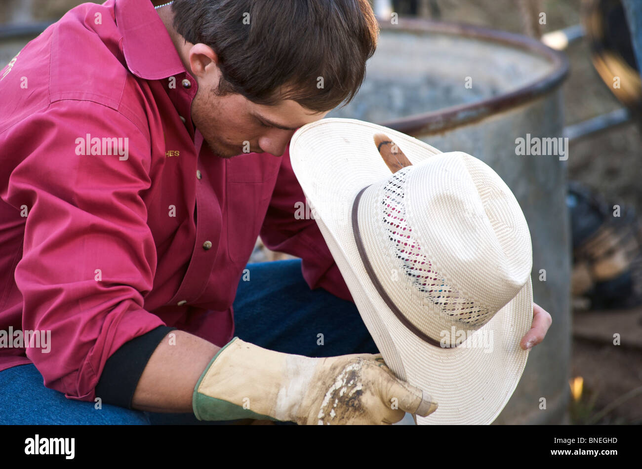 Cowboy sitting  holding hat looking disappointed after rodeo event at a   PRCA In Texas, USA - Stock Image