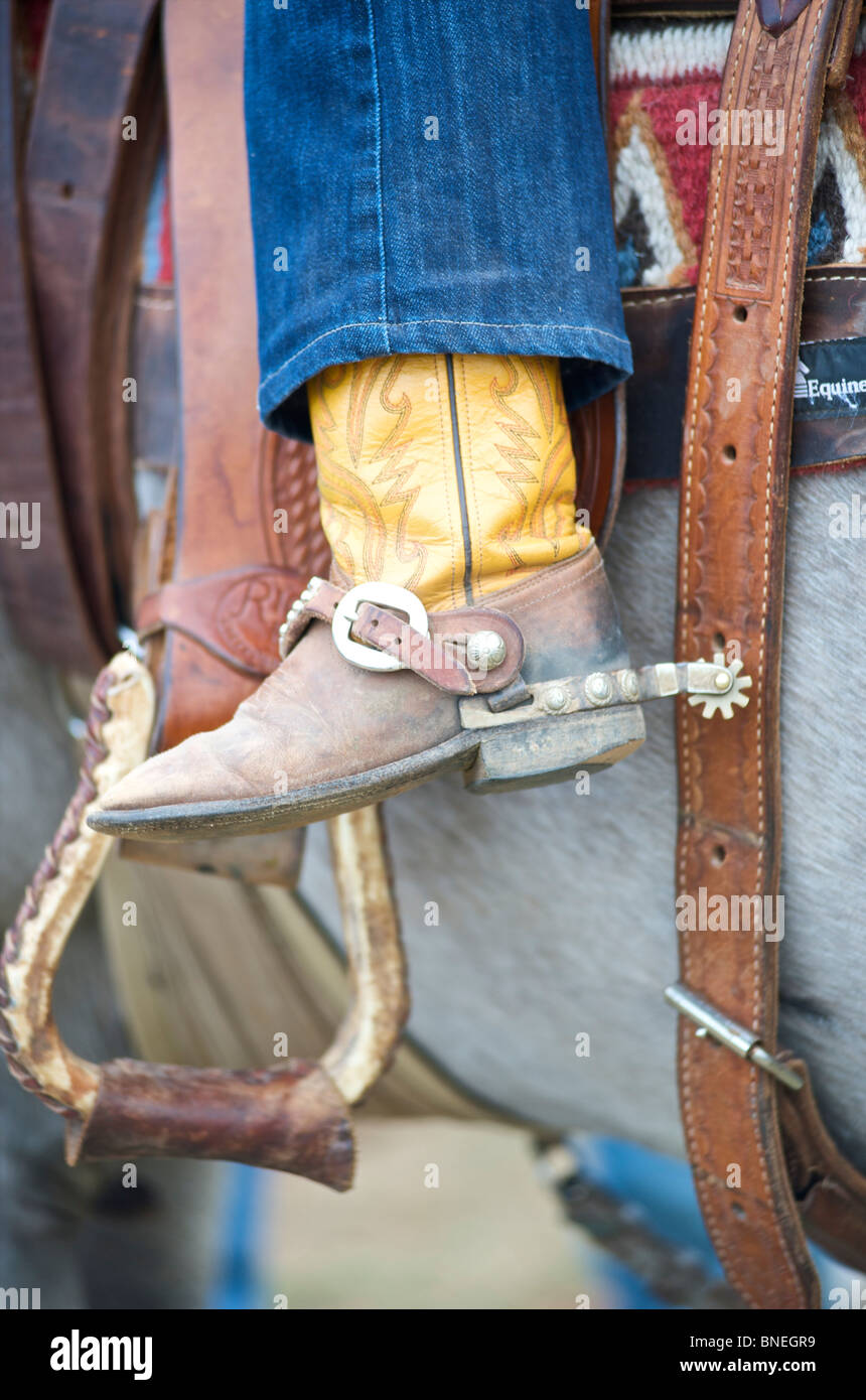 Boots and spurs of cowboy riding horse - Stock Image