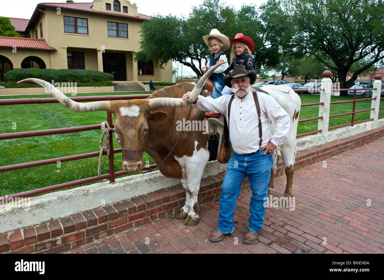 Children  on longhorns posing with grandfather in Fort Worth, Texas, USA Stock Photo