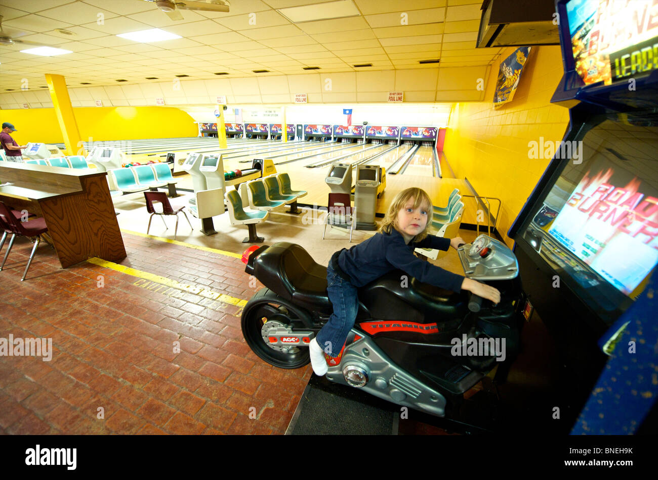 Three year old boy riding Motorcycle game in Bowling Hall Texas, USA Stock Photo