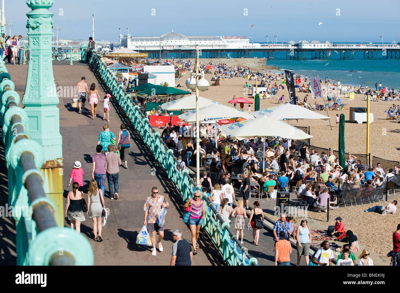 Crowded seafront and pebble beach, Brighton, East Sussex, United Kingdom - Stock Image
