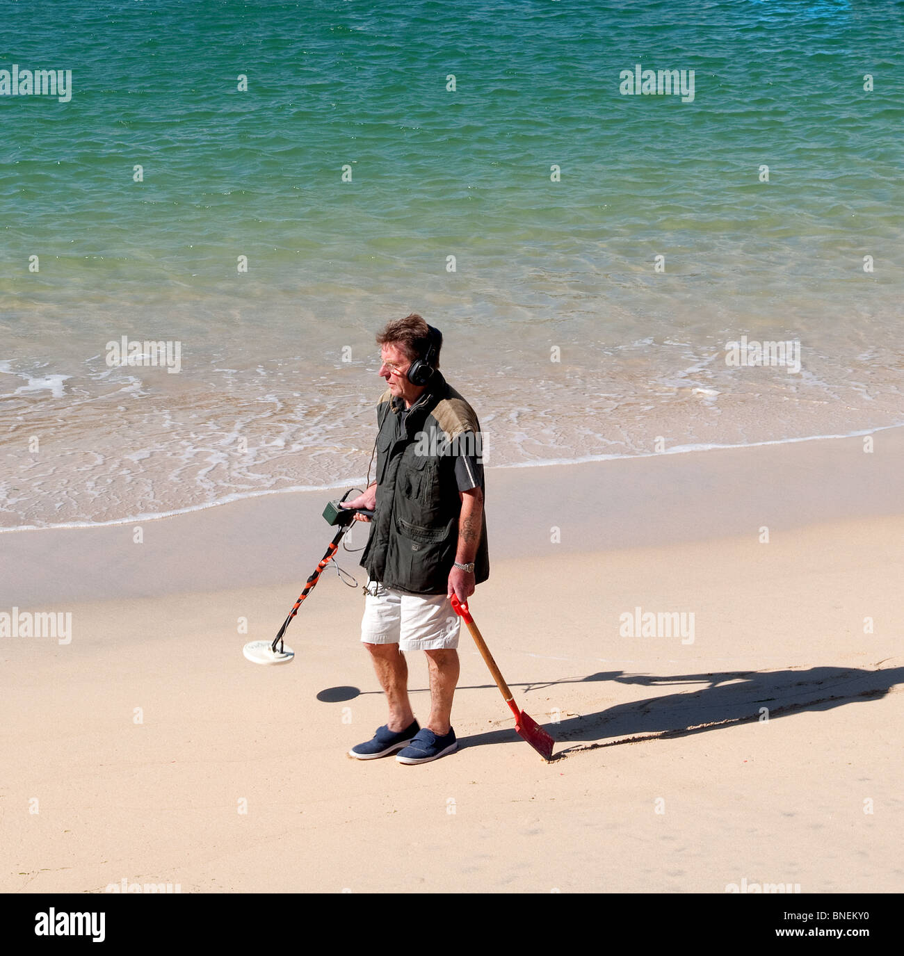a man using a metal detector on the beach, england, uk - Stock Image