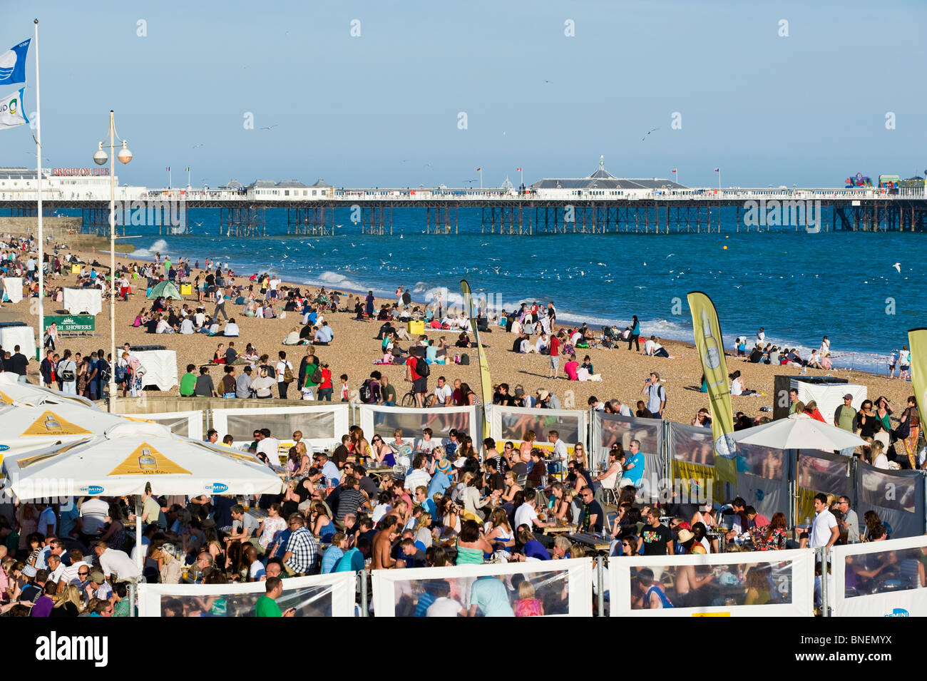 Crowded bars and beach on hot summer day, Brighton, East Sussex, United Kingdom - Stock Image