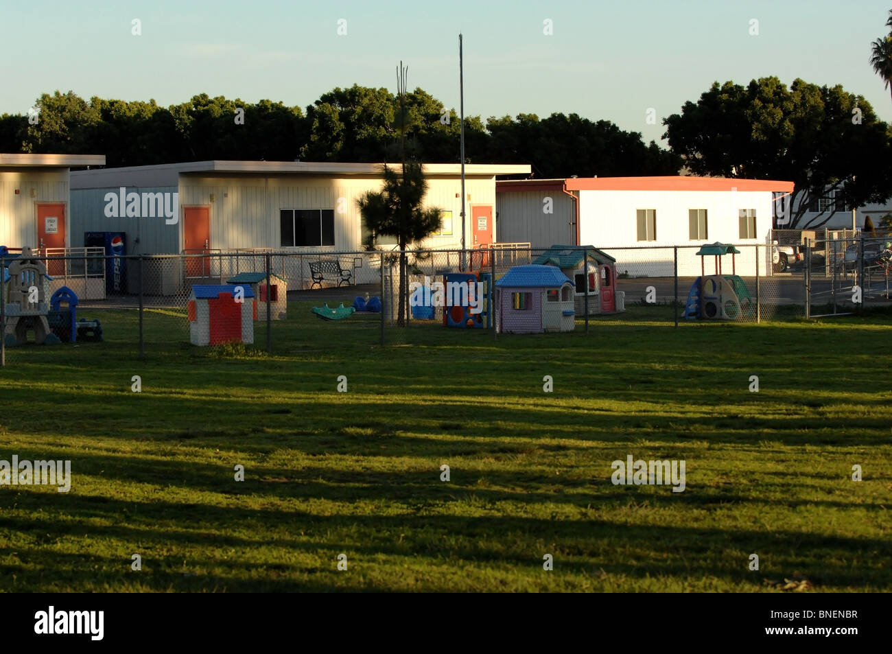 Daycare facility, empty of children, behind a short chain-link fence. Stock Photo