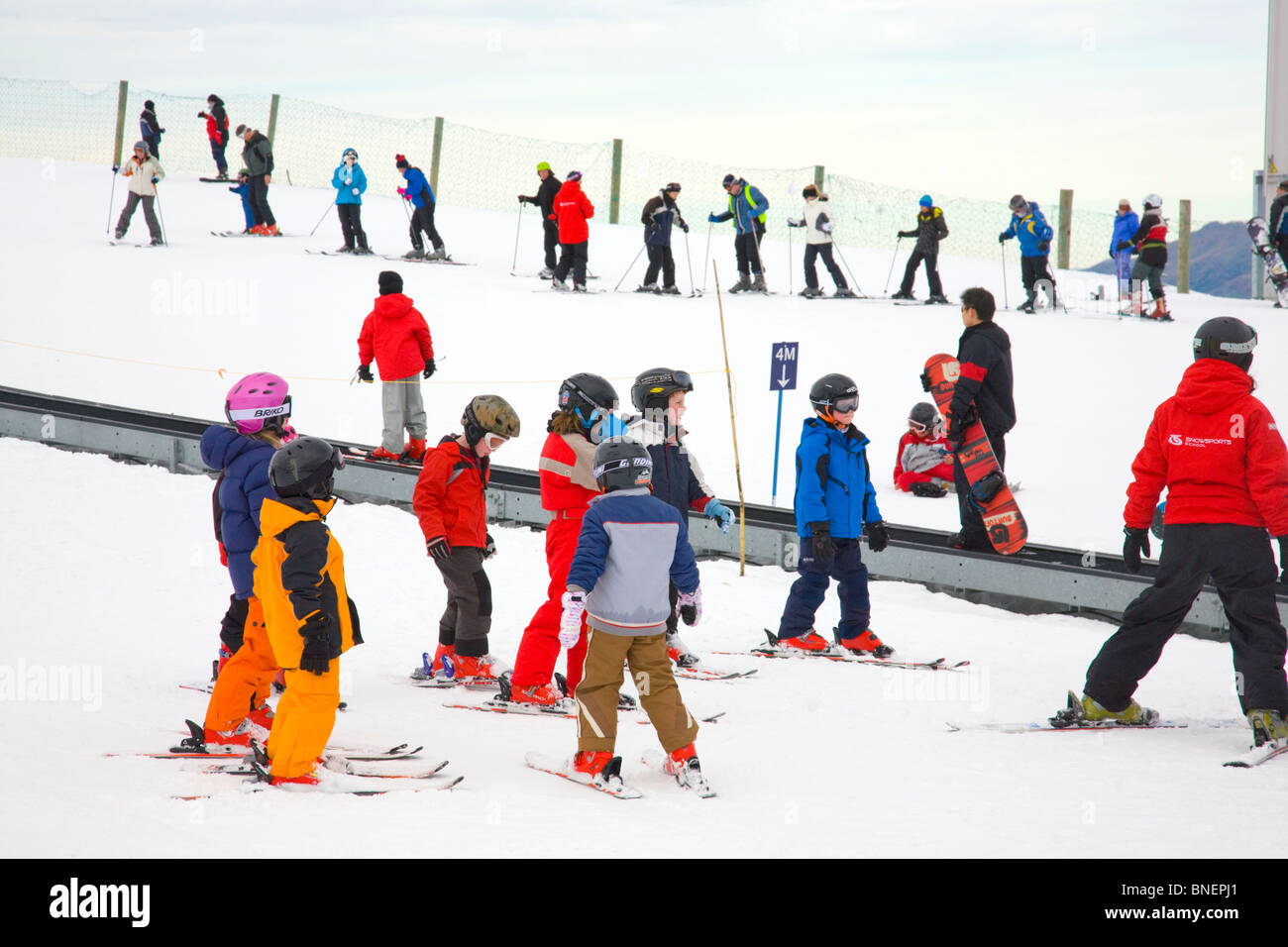 children with their ski instructor learning to ski at coronet peak ski resort whilst other learners travel on the - Stock Image