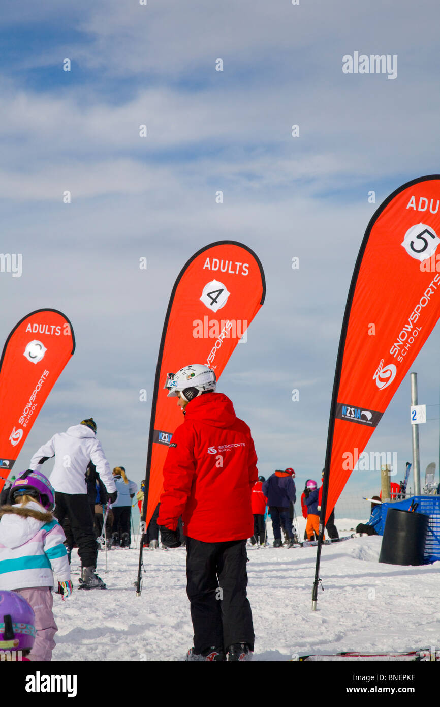 ski instructor walking by the banners to identify where adults should wait for their ski lesson, coronet peak - Stock Image