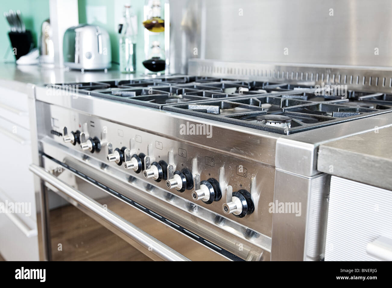 Close Up Shot Across Cooker in Modern Colourful Kitchen - Stock Image