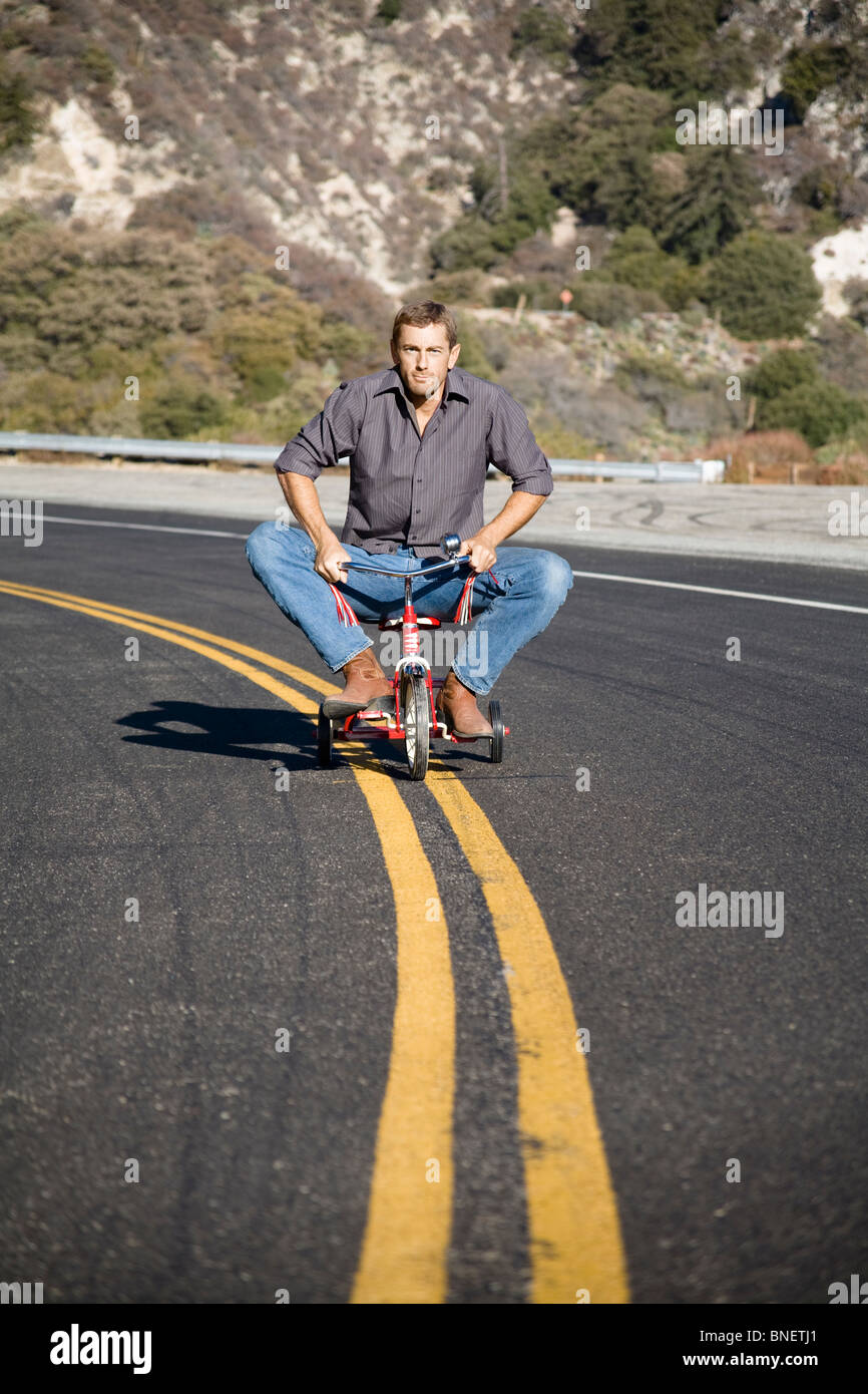 Man riding tricycle down the  middle of a street - Stock Image