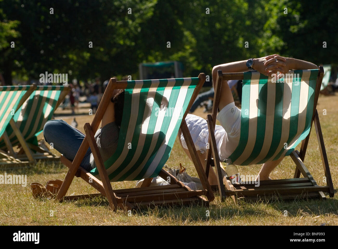 Deck chairs couple enjoy the summer sunshine during a mini heat wave hot weather Hyde Park London Uk HOMER SYKES - Stock Image
