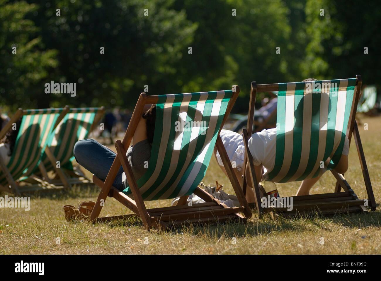 Heat wave hot weather couple deckchairs Hyde Park London Uk - Stock Image