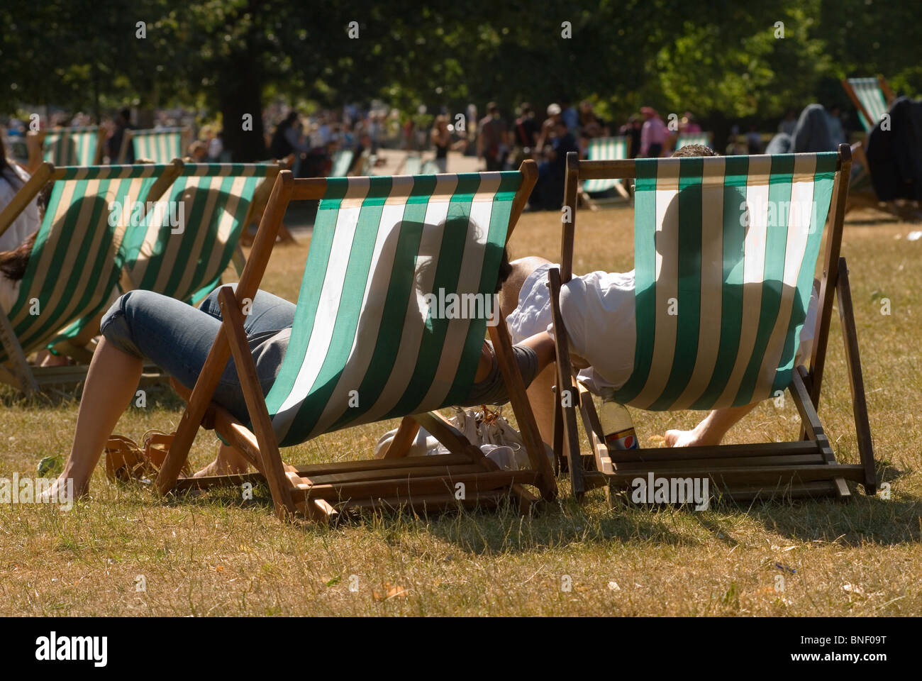 Heat wave hot weather couple deckchairs Hyde Park London Uk HOMER SYKES - Stock Image