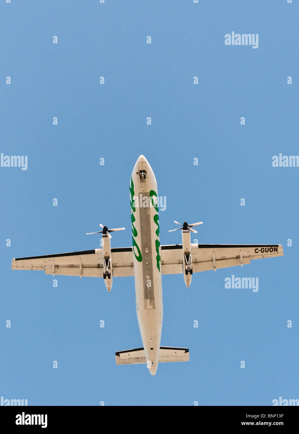 Looking straight up at an Air Canada Jazz Dash-8 commercial airliner on final approach for landing . Stock Photo
