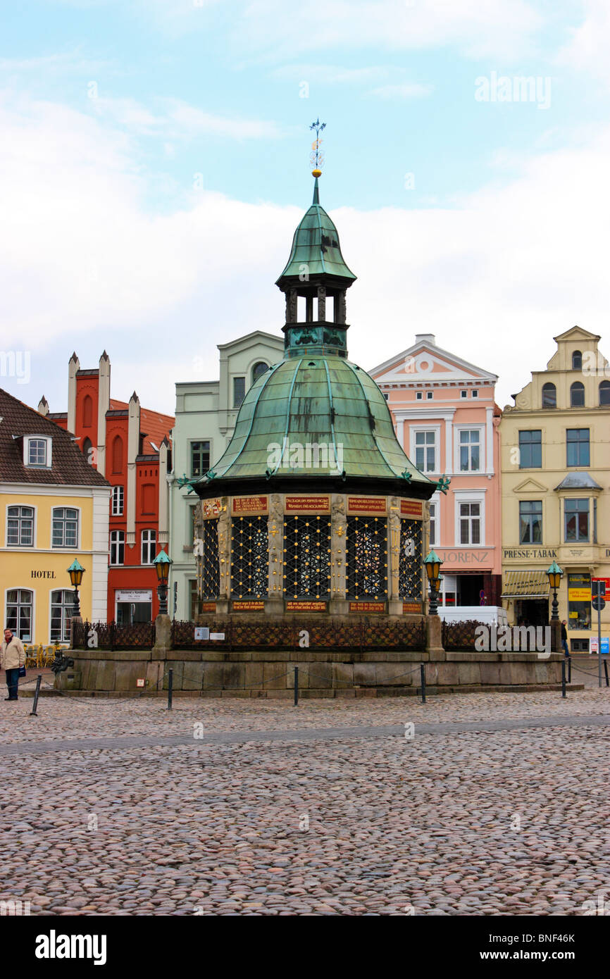 Fountain and ancient buildings around the market place in Wismar, Germany - Stock Image