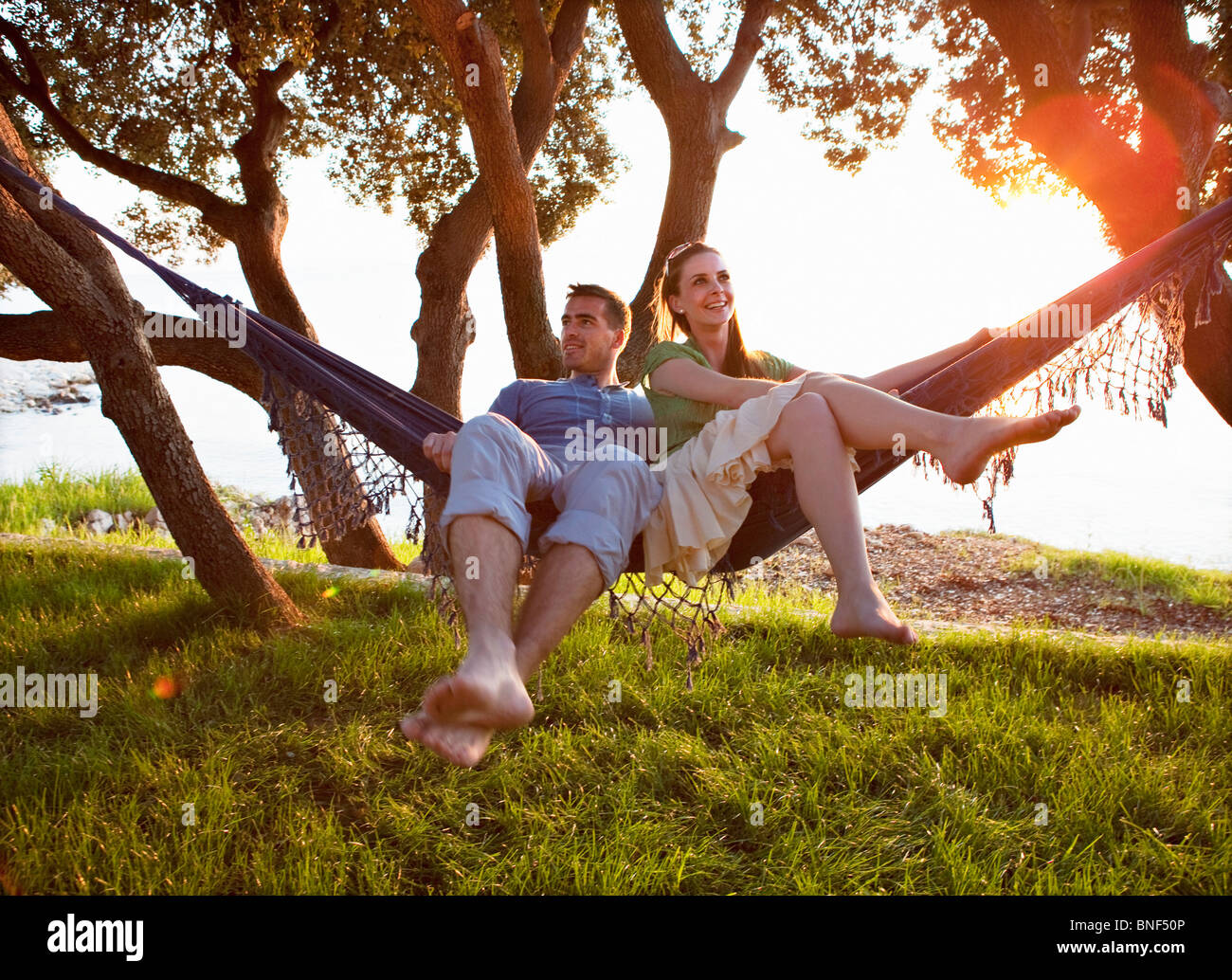 Couple lying in hammock at beach - Stock Image