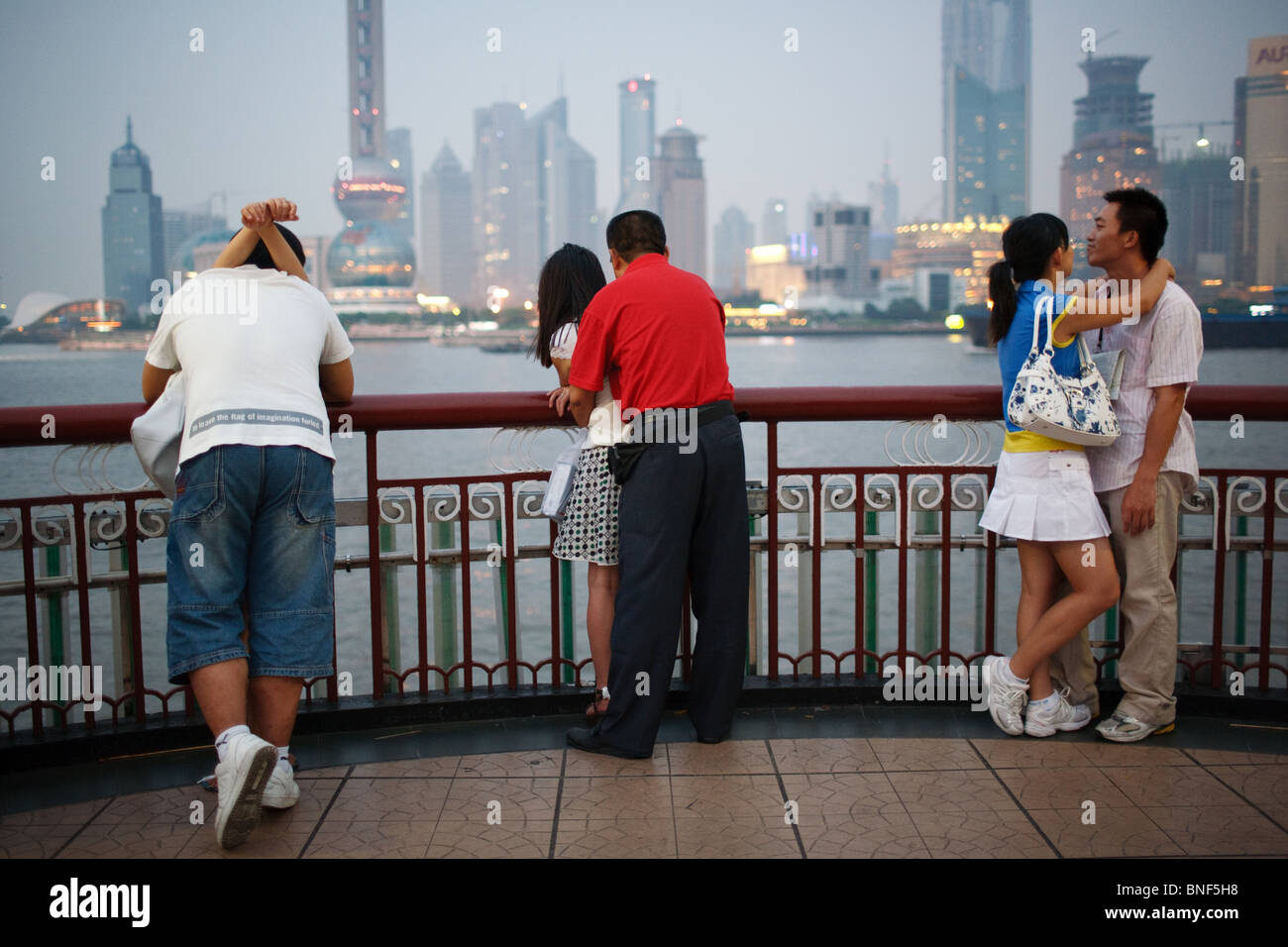 Young Chinese couples on the Bund promenade overlooking modern Pudong district in Shanghai, China, - Stock Image