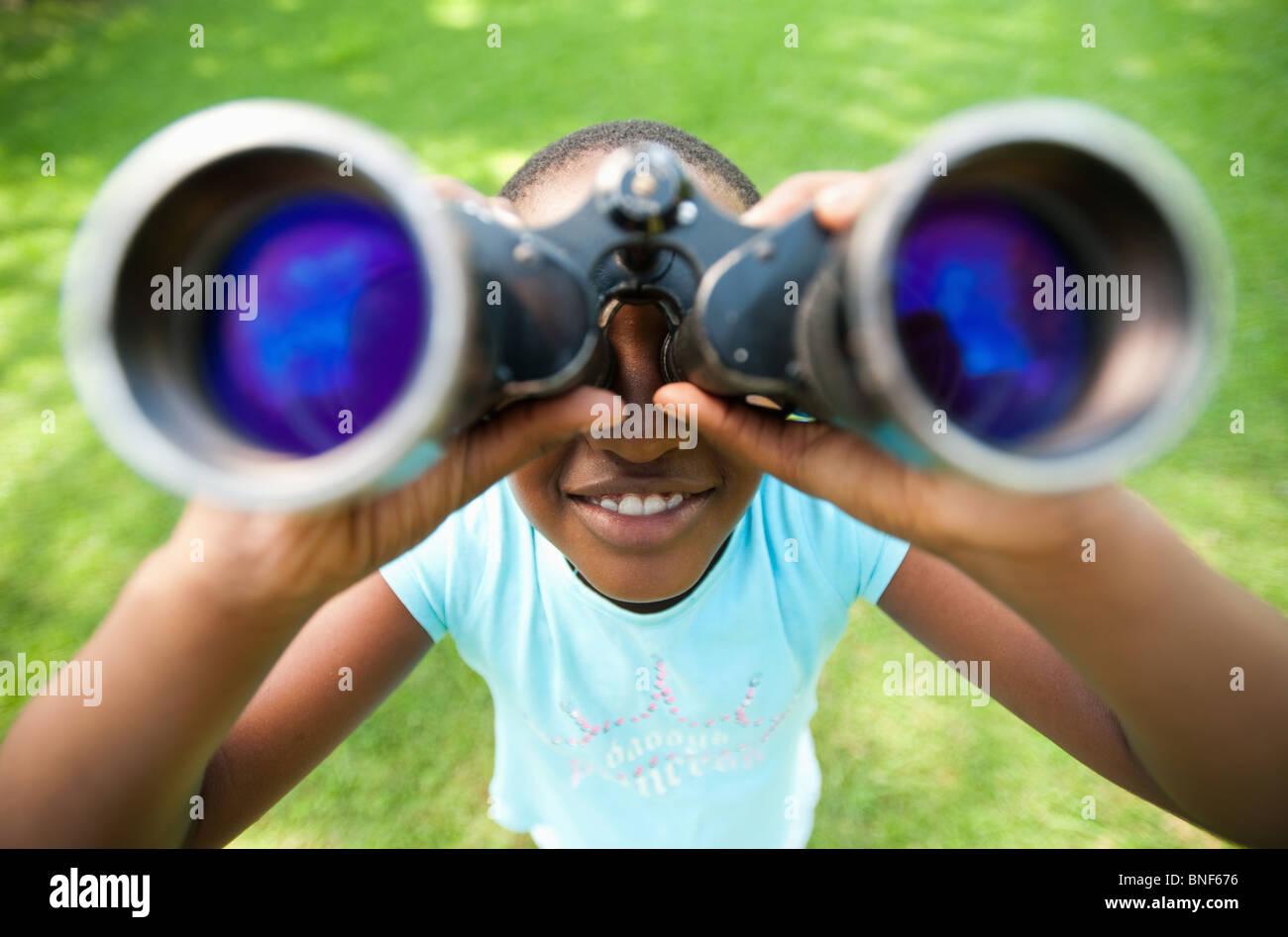 Portrait of girl (8-9) looking through binoculars, Johannesburg, Gauteng Province, South Africa - Stock Image